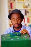 Homme avec du charme utilisant la chemise bleue et le chapeau se reposant par le cadeau d'anniversaire d'ouverture de table, rega Images libres de droits