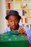 Homme avec du charme utilisant la chemise bleue et le chapeau se reposant par le cadeau d'anniversaire d'ouverture de table, rega Photographie stock libre de droits