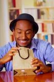 Homme avec du charme utilisant la chemise bleue et le chapeau se reposant par le cadeau d'anniversaire d'ouverture de table, rega Photo libre de droits