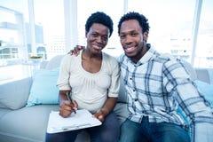 Homme avec l'écriture enceinte d'épouse sur le bloc-notes Photographie stock libre de droits