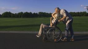 Homme avec l'épouse dans le fauteuil roulant appréciant dehors clips vidéos