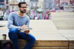 Homme avec l'événement de visite de téléphone portable pour intéresser des lecteurs travaillant dehors notant l'idée dans le plan images stock