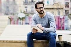 Homme avec l'événement de visite de téléphone portable pour intéresser des lecteurs travaillant dehors notant l'idée dans le plan photo stock