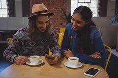Homme avec l'ami à l'aide du téléphone en café Image libre de droits