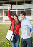 Homme avec l'ami faisant des gestes des klaxons de diable sur l'université Image stock