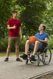 Homme avec l'ami sur le fauteuil roulant tenant un basket-ball Image libre de droits