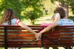 Homme avec l'amie tout en tenant des mains avec une autre femme Photos libres de droits