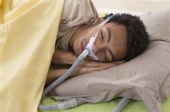 Homme avec l'apnea de sommeil utilisant une machine de CPAP Photographie stock