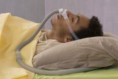 Homme avec l'apnea de sommeil utilisant une machine de CPAP Images stock