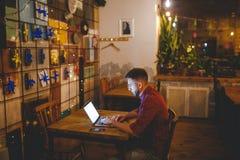 Homme avec l'homme d'affaires de barbe travaillant derrière l'ordinateur portable dans le café dans la soirée intérieur décoré du Photo libre de droits