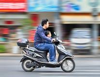Homme avec l'enfant sur un scooter électrique, Changhaï, Chine Photo libre de droits