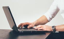Homme avec l'horloge sur ses travaux de main sur l'ordinateur portable à la table dans le bureau Il est occupé avec la tâche photographie stock libre de droits