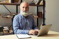 Homme avec l'ordinateur portable dans le bureau regardant l'appareil-photo et le sourire Images stock