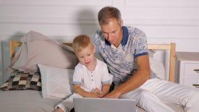 Homme avec l'ordinateur portable de observation de fils sur le lit banque de vidéos