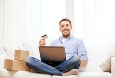 Homme avec l'ordinateur portable, la carte de crédit et les boîtes en carton Photo libre de droits