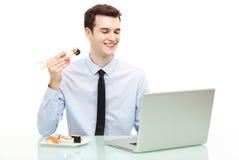 Homme avec l'ordinateur portable mangeant des sushi Photos stock