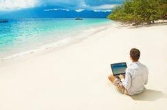 Homme avec l'ordinateur portable sur la plage colorée Photos stock