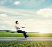 Homme avec l'ordinateur portable volant au-dessus de la route Photo libre de droits