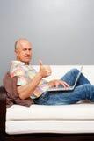 Homme avec l'ordinateur portatif à la maison affichant des pouces vers le haut Photographie stock