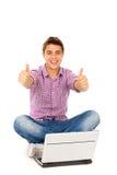 Homme avec l'ordinateur portatif affichant des pouces vers le haut Photographie stock libre de droits