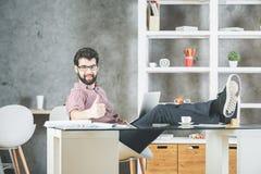 Homme avec l'ordinateur portatif affichant des pouces vers le haut Images stock