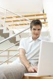 Homme avec l'ordinateur portatif sur des escaliers Photographie stock libre de droits