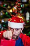 Homme avec la barbe dans le chapeau de Noël sur le fond de l'arbre image libre de droits