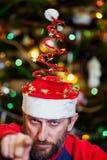Homme avec la barbe dans le chapeau de Noël sur le fond de l'arbre photographie stock libre de droits