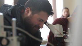 Homme avec la barbe regardant dans le microscope optique vissant vers le haut de son un oeil banque de vidéos