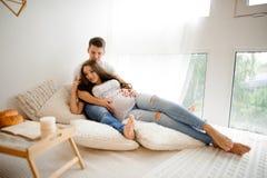 Homme avec la belle femme enceinte se trouvant sur le lit dans une salle blanche Images stock