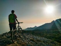 Homme avec la bicyclette au fond de montagnes photos libres de droits
