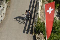 Homme avec la bicyclette et les drapeaux de la Suisse, vue supérieure d'Uetlibe Photographie stock libre de droits