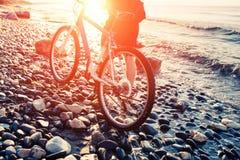 Homme avec la bicyclette sur un coucher du soleil de bord de mer Images stock