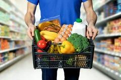 Homme avec la boîte à nourriture dans des mains à l'épicerie photographie stock libre de droits