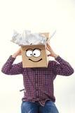 Homme avec la boîte de sourire au-dessus de sa tête Photographie stock