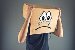 Homme avec la boîte en carton sur sa tête et expression triste de visage Photographie stock libre de droits