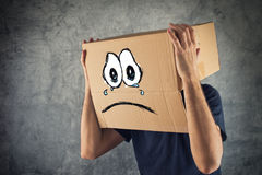 Homme avec la boîte en carton sur sa tête et expression triste de visage Images stock