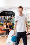 Homme avec la boule de bowling dans le club Image libre de droits