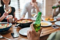 Homme avec la bouteille de bière se reposant et célébrant avec des amis Image libre de droits