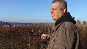 Homme avec la canne à pêche près du lac clips vidéos