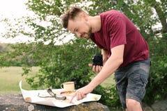 Homme avec la carte l'explorant d'appareil-photo dehors photo stock