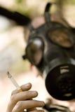 Homme avec la cigarette allumée par fixation de Gasmask Photographie stock libre de droits