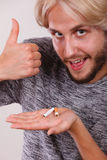 Homme avec la cigarette cassée sur la paume composant le pouce Photo stock