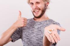 Homme avec la cigarette cassée sur la paume composant le pouce Photos stock