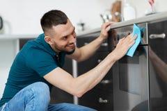 Homme avec la cuisine de porte de four de nettoyage de chiffon à la maison Photo libre de droits