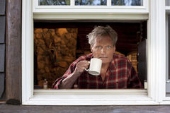 Homme avec la cuvette de café regardant hors de l'hublot Photo stock