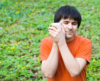 Homme avec la cuvette de café sur la nature photographie stock libre de droits