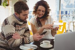 Homme avec la femme à l'aide du téléphone en café Image stock