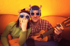 Homme avec la femme dans les verres drôles, jouant l'ukulélé Photo stock