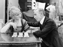 Homme avec la femme jouant le jeu de carte (toutes les personnes représentées ne sont pas plus long vivantes et aucun domaine n'e Photographie stock